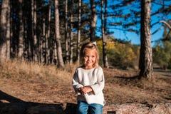 Den gulliga le lilla flickan spelar utomhus arkivbilder