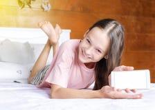 Den gulliga le preteenflickan i rosa t-skjorta och kortslutningar på säng visar hennes mobiltelefonskärm i bohostilrum mot den ga royaltyfria foton