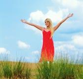 Den gulliga leendeung flicka som fördelar henne, beväpnar Arkivfoto