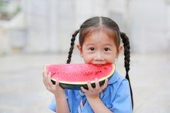 Den gulliga lilla asiatiska barnflickan i skolalikformig tycker om att äta den nya skivade vattenmelon royaltyfri fotografi