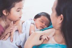 Den gulliga lilla asiatiska barnflickan som ser hennes nyfött, behandla som ett barn systern Arkivfoton