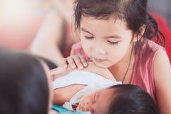 Den gulliga lilla asiatiska barnflickan som ser hennes nyfött, behandla som ett barn systern Royaltyfri Foto