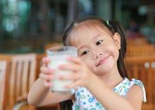Den gulliga lilla asiatiska flickan som rymmer exponeringsglas av, mjölkar i coffee shop arkivfoto