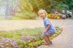 Den gulliga lilla blonda pojken som spelar i, parkerar att le arkivbilder