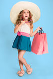 Den gulliga lilla caucasian brunettflickan i hållande shoppingpåsar för klänning royaltyfri foto