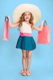 Den gulliga lilla caucasian brunettflickan i hållande shoppingpåsar för klänning royaltyfri bild