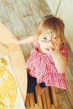 Den gulliga lilla dottern är bitande kakadeg i olika former Dottern hjälper hennes moder att baka kakor i ett kök Arkivbilder