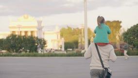 Den gulliga lilla dotterridningen på skuldrafadern som går i sommarstad, parkerar lager videofilmer
