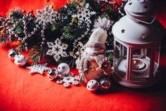Den gulliga lilla förtjusande snögubben står nära den vita felika lyktan och den dekorerade granträdfilialen bak den Royaltyfri Bild