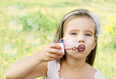 Den gulliga lilla flickan är att blåsa såpbubblor royaltyfria foton