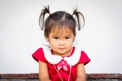Den gulliga lilla flickan är lyssnande musik på hörlurar Arkivfoton