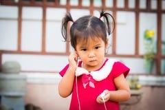 Den gulliga lilla flickan är lyssnande musik på hörlurar Royaltyfria Foton