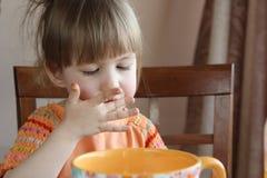Den gulliga lilla flickan äter Arkivbild