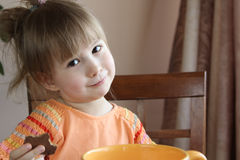 Den gulliga lilla flickan äter kakor fotografering för bildbyråer