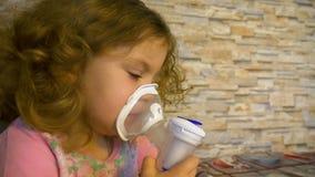 Den gulliga lilla flickan använder inandning close upp arkivfilmer