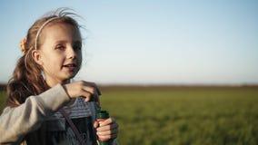 Den gulliga lilla flickan blåser såpbubblor i ängen på en solig dag långsam rörelse lycklig barndom suddighet bakgrund stock video