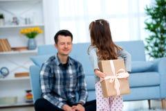 Den gulliga lilla flickan, dottern, syster ger en gåvaask till den unga den farsafadern eller brodern Båda ler Faders concep för  arkivbilder