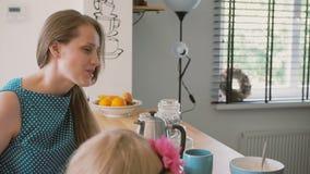 Den gulliga lilla flickan färgar, medan hennes mum har en konversation på köksbordet Långsam mo Steadicam skott lager videofilmer