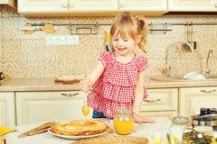 Den gulliga lilla flickan förbereder pannkakor och hällande honung på bunt av pannkakor Royaltyfri Foto