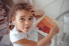 Den gulliga lilla flickan gör applique, limmar det färgrika huset som applicerar ett färgpapper genom att använda limpinnen, meda royaltyfri fotografi