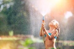 Den gulliga lilla flickan häller sig från slangen, gör ett regn varmt royaltyfri fotografi