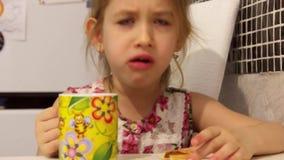 Den gulliga lilla flickan har ett frukostbarn som äter kakor och dricker te stock video