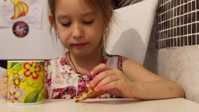 Den gulliga lilla flickan har ett frukostbarn som äter kakor och dricker te arkivfilmer