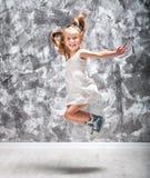 Den gulliga lilla flickan hoppar royaltyfri fotografi