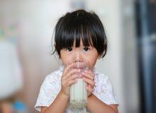Den gulliga lilla flickan, i att dricka för pyjamas, mjölkar från exponeringsglas inomhus på morgonen arkivfoto