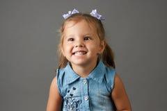 Den gulliga lilla flickan i blått klär att le och uppvisning av hennes tänder royaltyfria bilder