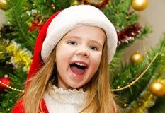 Den gulliga lilla flickan i den santa hatten med gåva har jul Arkivfoto