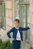 Den gulliga lilla flickan i en trendig dräkt står vid huset Royaltyfri Fotografi