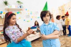 Den gulliga lilla flickan i enkrona ger gåvan till den frustrerade pojken i födelsedaghatt royaltyfria foton