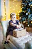 Den gulliga lilla flickan i lila klänningsammanträde i en stol och öppnar asken med gåva för bakgrundsjulgran royaltyfri bild