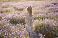 Den gulliga lilla flickan i sommarklänning står bland blomninglavendelfält Royaltyfria Bilder