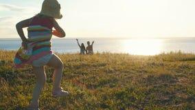 Den gulliga lilla flickan kör in i händerna av föräldrar arkivfilmer