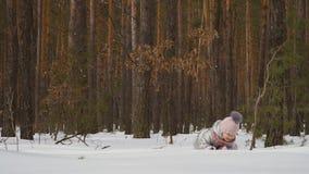 Den gulliga lilla flickan kryper på den insnöade vinterskogen stock video