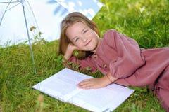 Den gulliga lilla flickan ligger på grönt gräs och läser boken arkivbild