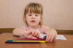 Den gulliga lilla flickan målar och grejar med kulöra blyertspennor och sax arkivbilder