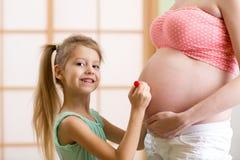 Den gulliga lilla flickan målar på buken av henne royaltyfria foton