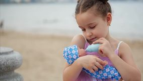 Den gulliga lilla flickan matar hennes favorit- docka från en leksakflaska Det lilla barnet som spelar med dockan i, parkerar vid lager videofilmer