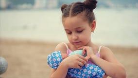 Den gulliga lilla flickan matar hennes favorit- docka fr?n en leksakflaska Det lilla barnet som spelar med dockan i, parkerar vid stock video
