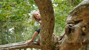 Den gulliga lilla flickan med blåa ögon och blont hår döljer barfota bak filialen av det stora trädet i parkerar under lager videofilmer