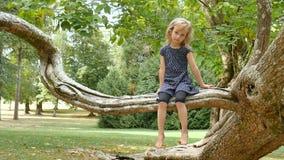 Den gulliga lilla flickan med blåa ögon och blont hår som barfota sitter på trädfilial i, parkerar under sommardag arkivfilmer