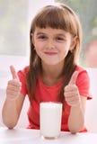 Den gulliga lilla flickan med ett exponeringsglas av mjölkar Arkivbilder