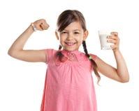 Den gulliga lilla flickan med exponeringsglas av mjölkar royaltyfria foton