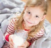 Den gulliga lilla flickan med exponeringsglas av mjölkar Arkivfoto