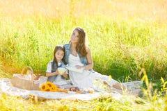 Den gulliga lilla flickan med hennes gravida moder har en picknick, lyckaögonblick i familjlivsstil royaltyfri fotografi
