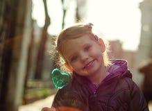 Den gulliga lilla flickan med hjärta formade godisen som in camera ler Royaltyfria Foton