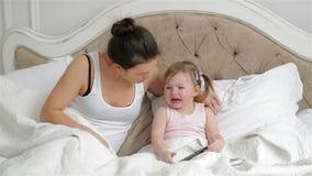 Den gulliga lilla flickan med två hästsvansar är skriande sammanträde på sängen Modern försöker att lugna hennes dotter i sovrumm lager videofilmer